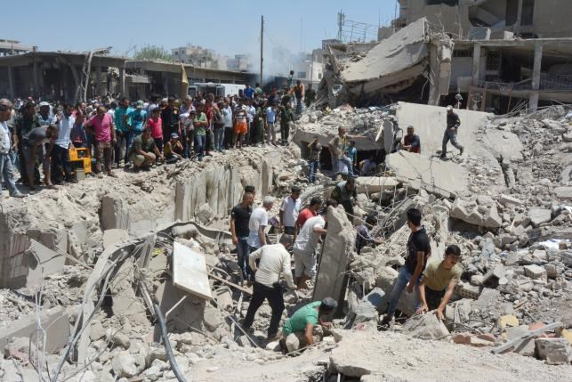 People look for survivors under debris at a damaged site after two bomb blasts claimed by Islamic State hit the northeastern Syrian city of Qamishli near the Turkish border, Syria July 27, 2016. Photo: Reuters/Rodi Said