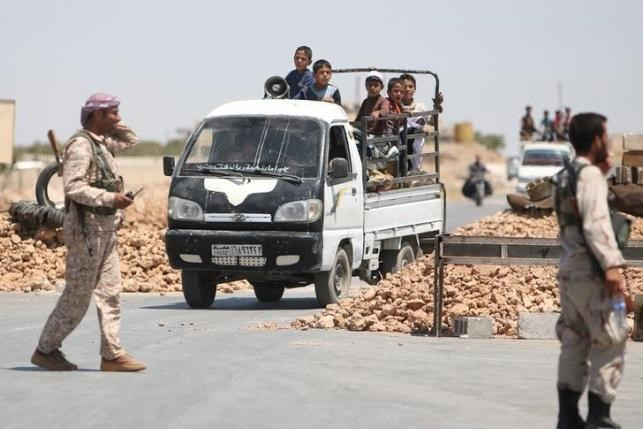 Syria Democratic Forces (SDF) fighters man a checkpoint as civilians on pick-up trucks evacuate from the southern districts of Manbij city after the SDF advanced into it in Aleppo Governorate, Syria, July 1, 2016. Photo: Reuters/Rodi Said