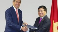 Foreign Minister Pham Binh Minh (R) shakes hands with US Secretary of State John Kerry after the signing of a bilateral civilian nuclear pact on the sidelines of the East Asia Summit in Brunei on October 10, 2013