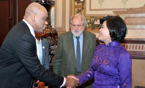Nguyen Thi Hong (R), deputy chairwoman of the HCMC People's Committee, shakes hands with UK Consul General in HCMC Douglas Anthony Barnes while receiving the UK delegation led by Lord Puttnam (C) February 27/ Photo: Saigon Times Daily