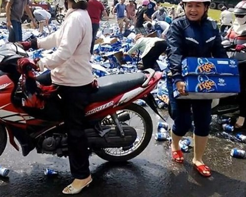 People rush to grab the beer cases and cans scattered on the ground in Bien Hoa City on December 4, 2013