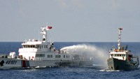 A Chinese ship blasts a Vietnamese vessel with a water cannon while guarding an oil rig illegally operating in Vietnamese waters. Photo credit: Reuters