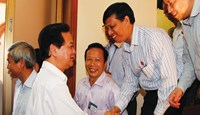 Prime Minister Nguyen Tan Dung (L) shakes hand with voters in the northern city of Hai Phong on May 15