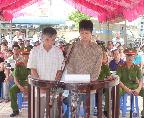 Dinh Van Vinh, 47, and Tran Anh Cuong, 30, stand trial for looting beer which fell off a truck in Dong Nai last year on July 8. Photo: Le Lam