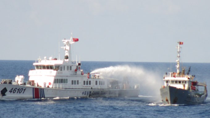 A file photo shows a Chinese ship firing a water cannon at a Vietnamese fisheries surveillance vessel in May