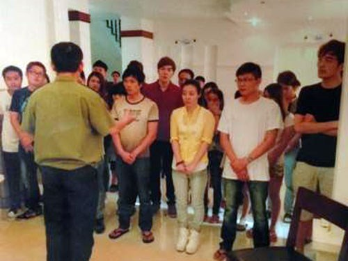 A police officer in Ho Chi Minh City talks to 26 Chinese and Taiwanese nationals who were caught in the city July 14, 2014 for making phone calls to cheat people's money