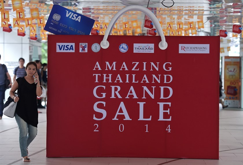 A tourist (L) walks past an advert for a shopping mall in Bangkok on August 14, 2014. Photo: AFP