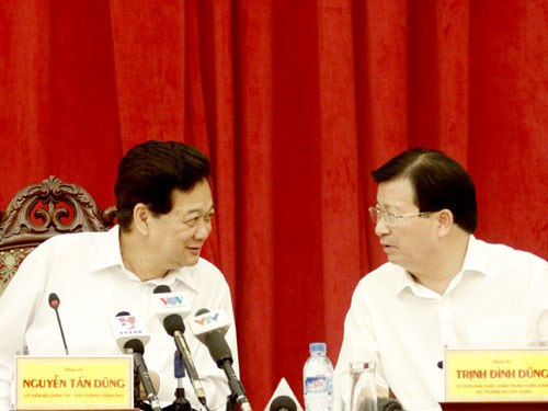 Prime Minister Nguyen Tan Dung (L) talks to Minister of Construction Trinh Dinh Dung at a meeting Thursday. Photo: Le Quan