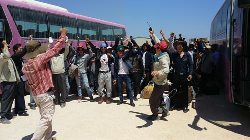 Vietnamese workers cheer after being sent home from Libya in July. Photo: V.Ha