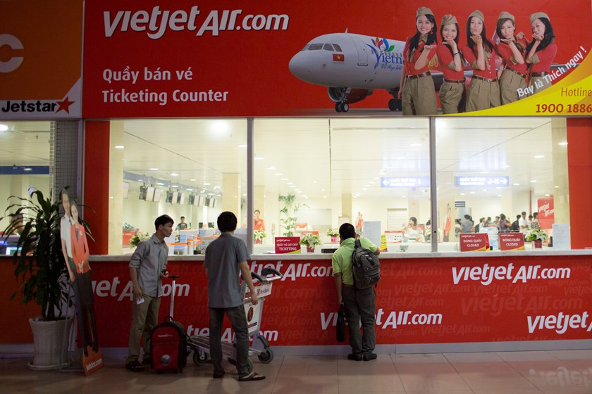 Passengers stand at a ticket counter for VietJet Air, operated by VietJet Aviation Joint Stock Co., at Tan Son Nhat International Airport in Ho Chi Minh City. Photo: Bloomberg