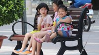 Children sit on a newly-installed wooden bench on Nguyen Hue Street. Photo credit: VnExpress