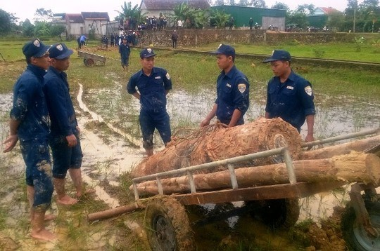 Sappers remove the bomb out of the paddy field. Photo credit: Huy Toan/Nguoi Lao Dong