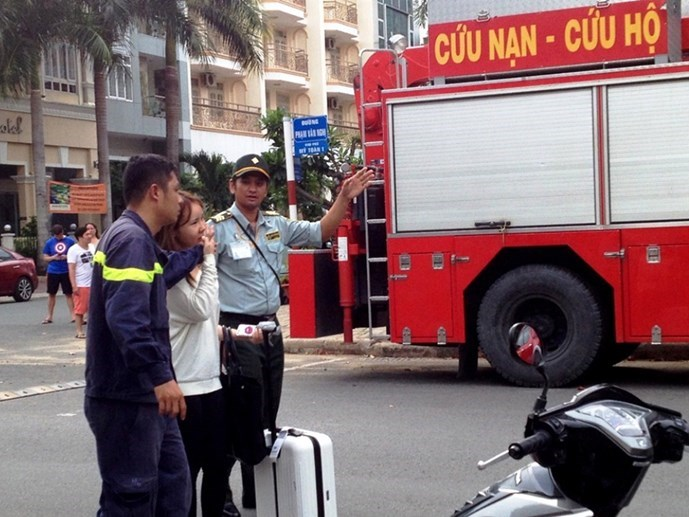A firefighter and a security guard escort a Korean woman out of a hotel in Dist. 7 after she threatened to jump from the third floor of her hotel room. Photo: Duc Tien