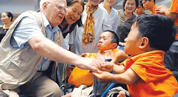 A file photo shows Len Aldis with young victims of Agent Orange in Vietnam. Photo credit: Saigon Giai Phong