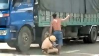 A still from a video that shows the policeman holding on to the leg of the truck driver