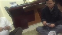 A still from the video clip shows four men playing cards in an office