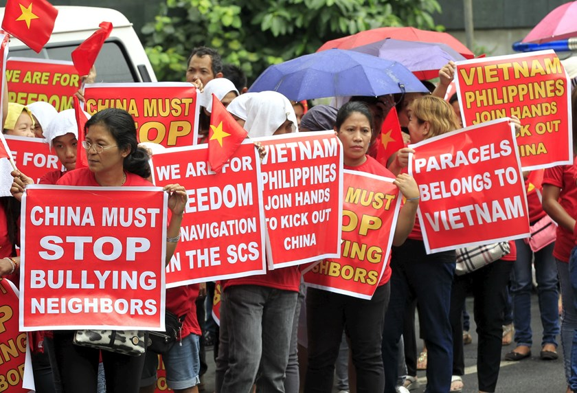 Protesters hold placards as they join in a protest rally to denounce China's military buildup in the South China Sea, in front of the Chinese Consulate in Makati city, metro Manila February 25, 2016. Photo credit: Reuters
