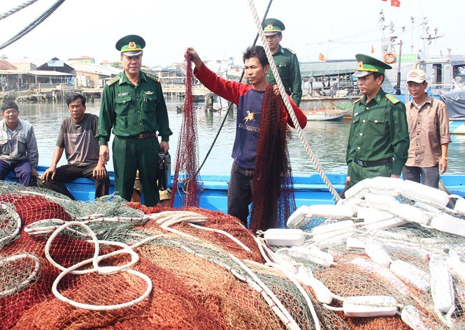 A crew member of the fishing boat that was robbed by Chinese forces on March 6 shows the broken fishing nets. Photo: Hua Xuyen Huynh
