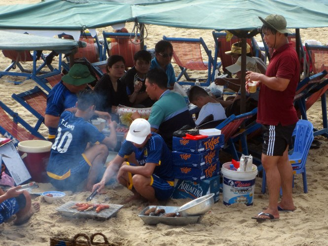 A group of tourists eat and drink on a Vung Tau beach. Photo: Nguyen Long