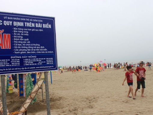 Tourists walk by a board listing officials' hotlines at Sam Son beach in Thanh Hoa Province. Photo credit: Tuoi Tre