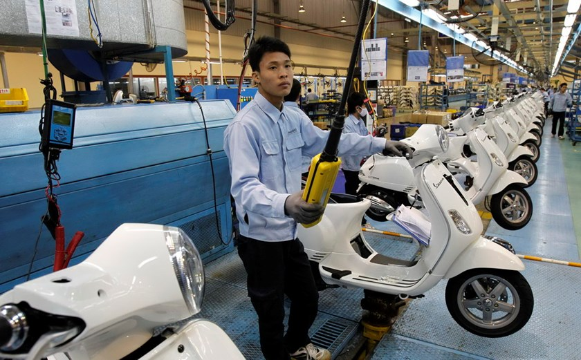 Men work on the assembly line at a Piaggio scooter and motorcycle factory in Vinh Phuc Province, outside Hanoi. Photo credit: Reuters