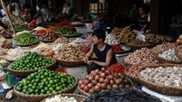 Traders wait amongst baskets containing fresh produce on sale at a wholesale market in downtown Hanoi. Photo credit: AFP