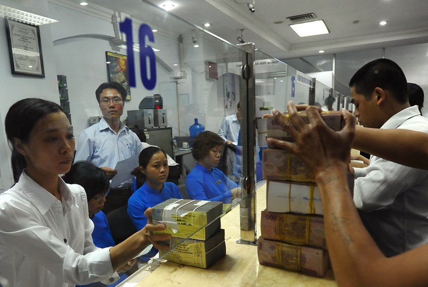 An Asia Commercial Bank employee (L) hands over bricks of bank notes to a customer withdrawing cash in Hanoi. VIetnam has been trying to restructure is banking system now laden in bad debts. Photo credit: AFP