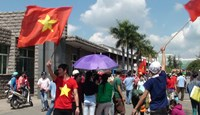 Protesters wave Vietnamese flags on a street outside a factory in Binh Duong Province on May 13 to protest China's illegal deployment of an oil rig in Vietnamese waters. Photo credit: AFP