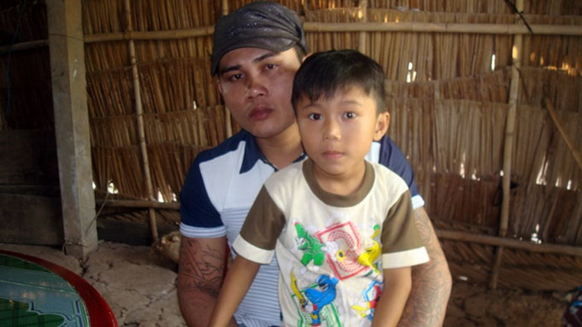 Thach So Phach with his son in Soc Trang Province after released February from a seven-month detention for a murder he did not commit. Five other men were wrongfully detained just like him and a woman for not reporting them. Photo credit: Tuoi Tre