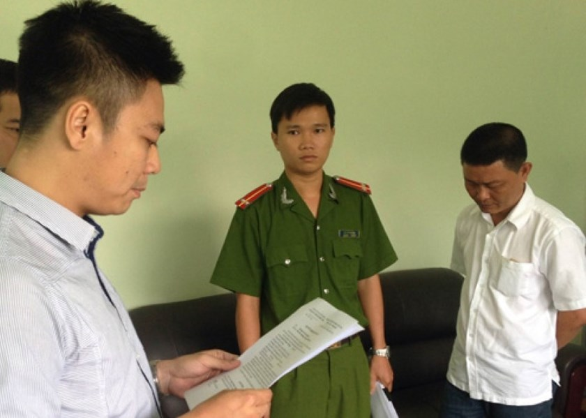 Customs official Nguyen Phuoc Tuong, 45, (L) is arrested in Ho Chi Minh City June 6 for letting 10 smuggled containers pass a port unchecked in December.