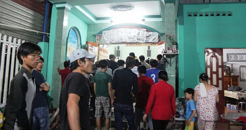 Locals gather at Huynh Kim Bao's house in Ho Chi Minh City the night of June 14 as he was brought home after being shot dead allegedly by the dog thieves he was chasing after. Photo: Ma Phong