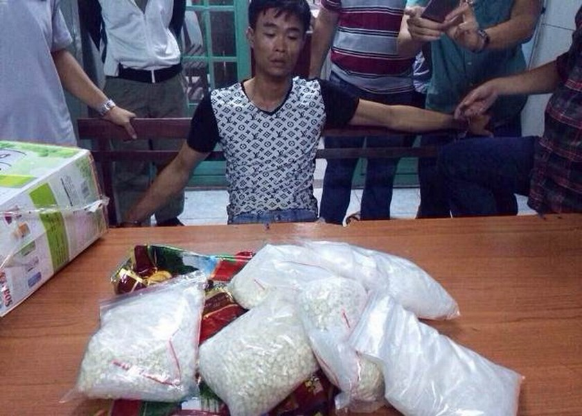 Pham Van Hoang, 30, at a HCMC police station with more than 7.1 kilograms of meth and ecstasy pills he was allegedly hired to smuggle from Hai Phong June 6. Photo credit: Lao Dong