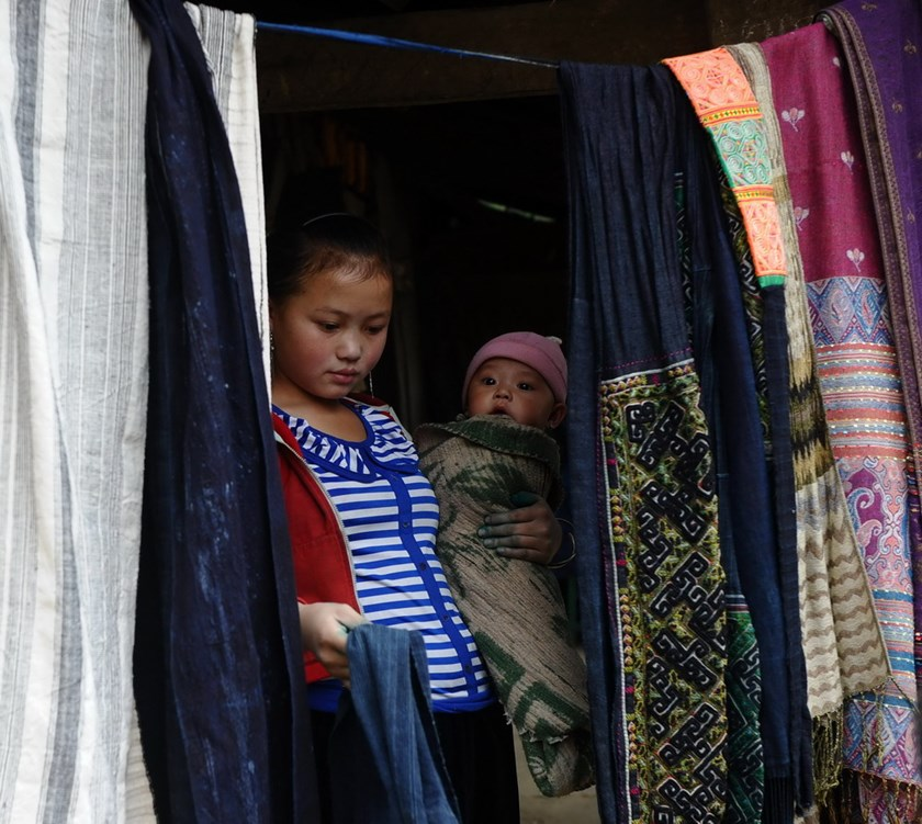A 16-year-old H'Mong ethnic mother with her 6-month-old son sells H'Mong traditional materials as souvenir items to visitors in Sapa, Lao Cai Province December 2013. Photo credit: AFP