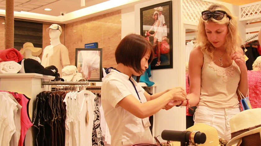 A Russian tourist (R) tries a bracelet at a fashion shop in Nha Trang. Photo credit: Tuoi Tre
