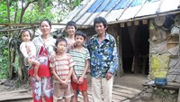 A Sang, 50, (R) with his wife and children outside their house deep in the jungle of Binh Thuan Province. Photo credit: Tuoi Tre