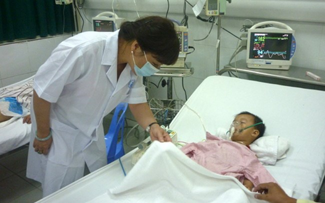 Health minister Nguyen Thi Kim Tien visits a 2-year-old encephalitis patient at the Central Pediatrics Hospital in Hanoi June 25. Photo credit: VietNamNet