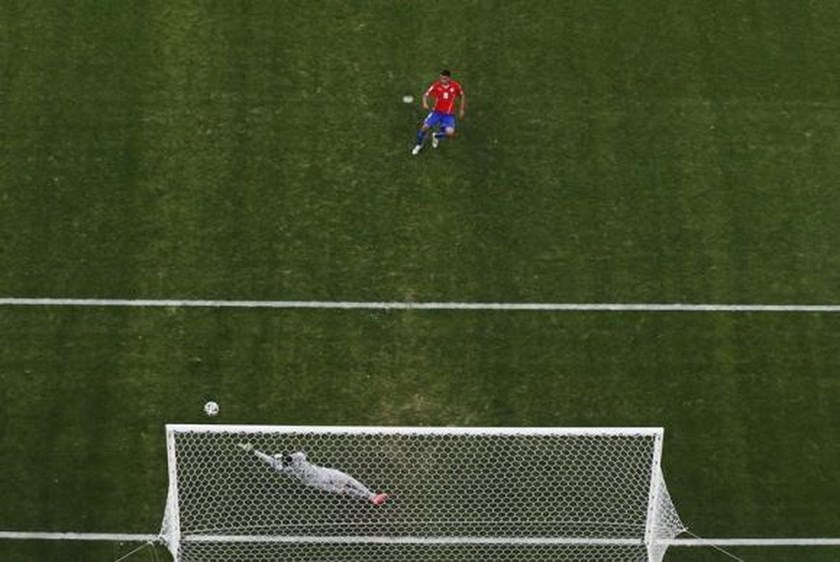 Chile's Gonzalo Jara takes a shot during a penalty shootout against Brazil, which missed and hit the goal post, in their 2014 World Cup round of 16 game at the Mineirao stadium in Belo Horizonte June 28, 2014. Photo credit: Reuters