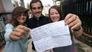 Quentin Dewiere (C), his wife Agnieszka Nanaszko (R) and a Western friend they just met in Vietnam, raise a note they had asked a local to write so they can use to ask for free ride and cheap service around the country. Photo credit: Tuoi Tre