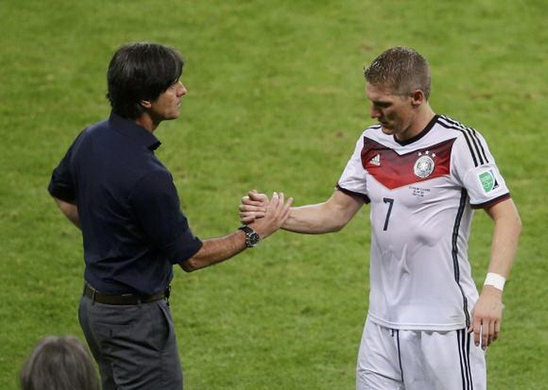 Germany's coach Joachim Loew (L) shakes hands with player Bastian Schweinsteiger as he leaves the field after sustaining an injury during extra time in their 2014 World Cup round of 16 game against Algeria at the Beira Rio stadium in Porto Alegre June 30
