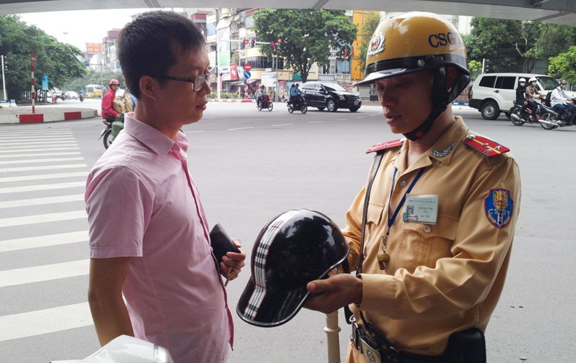 A police officer in Hanoi explains the new crash helmet rule to a motorist who was stopped for wearing a cap-shaped helmet, which does not follow standards, July 1, 2014. Photo credit: Thanh Nien