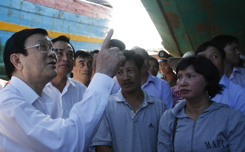 President Truong Tan Sang (L) points to damaged fishing boat DNA90152, which was rammed and then sunk by Chinese vessels on May 26, not far from where China has parked an oil rig in the disputed East Sea. Photo credit: Reuters