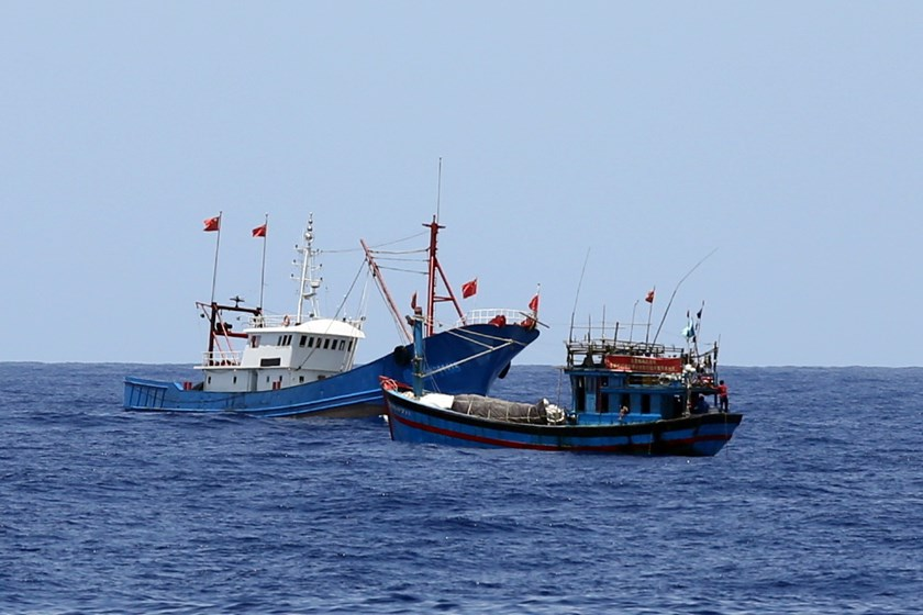 (L-R) A Chinese steel boat sails close to a Vietnamese wooden boat in the latter's water off Da Nang. China has sent numerous boats to guard an illegal oil rig it placed in Vietnamese waters from May and to attack any local fishing or coast guard boats th