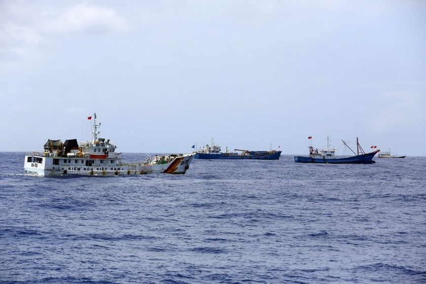 (L-R) A Vietnamese coast guard ship sails near local fishing boats in central Vietnam waters, which have been stirred up by China illegally placing an oil rig and sending numerous vessels to protect it since the beginning of May 2014. Photo: Doc Lap