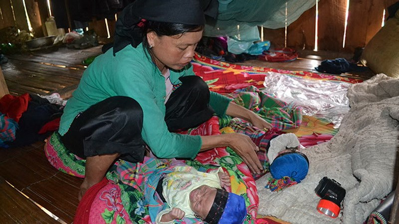 Lu Thi Bien, 27, takes care of her twin children born month apart between May 4 and June 5, 2014, according to her and commune officials in Ha Giang Province. Photo credit: Tuoi Tre