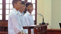 Three school boys stand behind bars at an appeal court in Hai Phong July 8, 2014 asking for reduced sentences after they were charged of robbery for taking two girls' hats worth less than US$3. Photo credit: Lao Dong