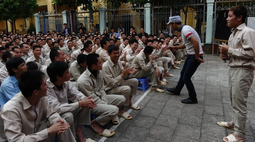 A drug addict inmate (R) and a singer (2nd R) sing together in front of other inmates during a music show organized by a group of local artists to mark the World Aids Day at a rehab in Hanoi November 29, 2013. Photo credit: AFP