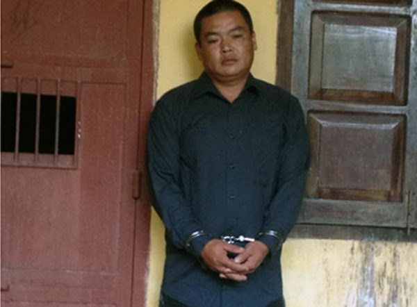 A photo provided by police in Quang Ninh Province shows Hoang Quoc Viet, 33, being handcuffed after causing a series of road crashes that killed a person and injured four others when speeding a robbed car July 14, 2014