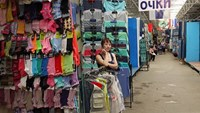 A Vietnamese guards her clothes booth at a market for Vietnamese traders in Donetsk in eastern Ukraine, where business has slowed down due to military tension with rebel militants. Photo credit: Dan Viet