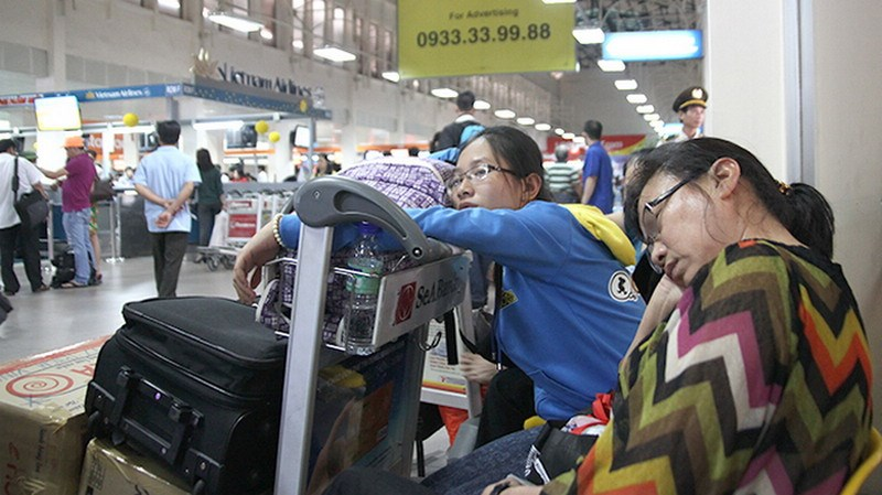 Two women wait for checking in at Tan Son Nhat airport in Ho Chi Minh City. Photo credit: Tuoi Tre