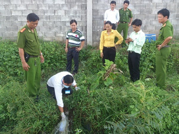 An official from Hau Giang Province's environment police take a sample of untreated water discharged from Nam Song Hau Seafood JSC through a buried pipe July 16, 2014. Photo: Vi Thanh